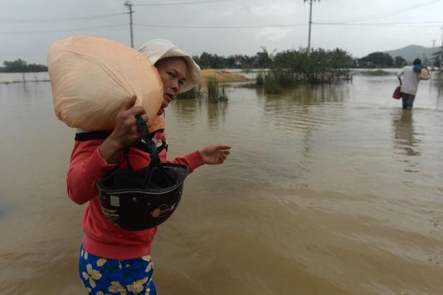 Chị Lê Thu Liên (36 tuổi) vác túi gạo lội nước về nhà nấu cơm trưa cho gia đình.