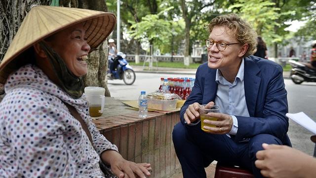 Ông Hogberg chăm chú lắng nghe người bán trà miêu tả cách thức pha trà mạn của Việt Nam.