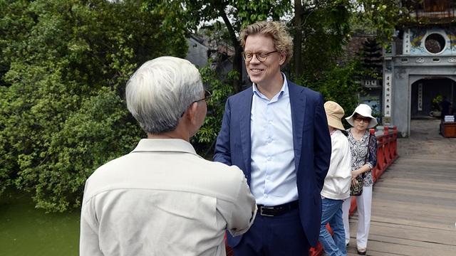 Nhà ngoại giao Thụy Điển dừng chân trên cầu và trò chuyện với một người Việt cũng tới thăm đền Ngọc Sơn.