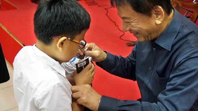 Ông Sugi bóc kẹo cho một học sinh khiếm thị.