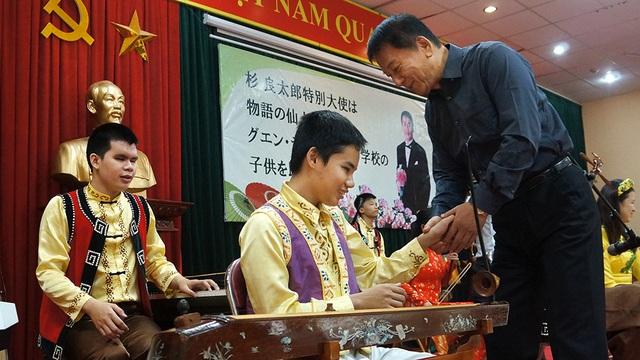 Đại sứ Ryotaro Sugi nắm tay các học sinh, động viên các em vượt qua khó khăn để vươn lên trong cuộc sống.