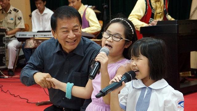 Đại sứ Hữu nghị Ryotaro Sugi nắm tay các em nhỏ đang trình diễn bài hát Chiếc đèn ông sao.