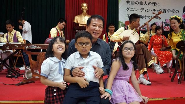 Đại sứ Sugi thận thiện ôm các cháu nhỏ vào lòng và vui đùa.