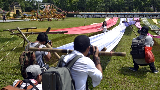 Những tay máy với ống kính máy móc lỉnh kỉnh đang sáng tác cho một thiếu nữ áo dài xinh xắn bên những dải lụa đầy sắc màu của làng nghề truyền thống lụa Vạn Phúc - Hà Đông.