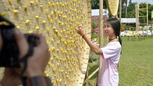 Tạo dáng bên nong tằm vàng óng được trung bày ở không gian hội chợ.