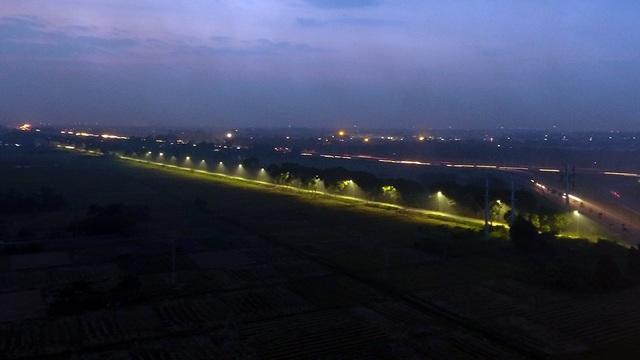 Tuyến đường ngoại ô thành vệt vàng rõ nét do đèn đườn kết hợp với mật độ khói bụi dày đặc.