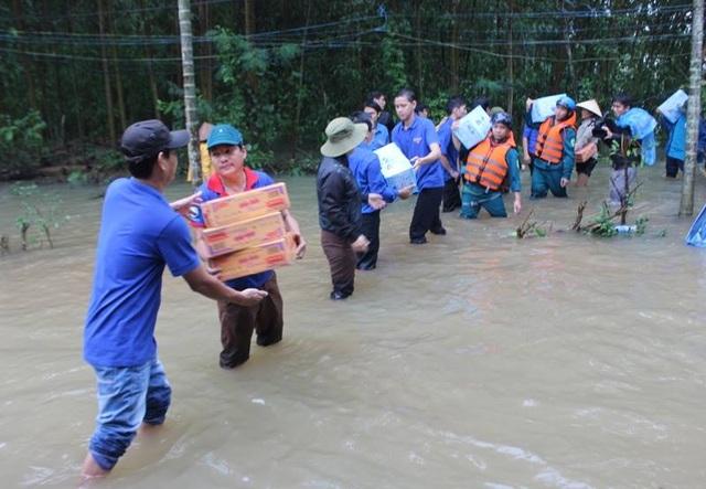 Các lực lượng chức năng, đoàn thể địa phương tham gia tiếp tế mì tôm, nước uống cho người dân trong vùng lũ
