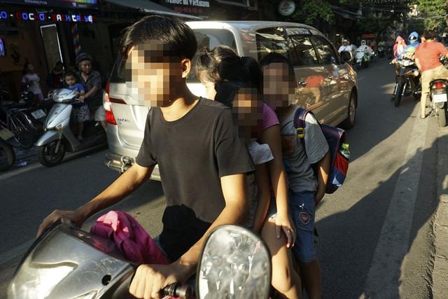 Hình ảnh thường thấy gần một trường tiểu học trên phố Hàng Buồm giờ tan học. Người lái xe chở đến ba em nhỏ, không em nào đội mũ bảo hiểm.