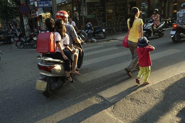 Một xe máy chở ba cháu nhỏ không đội mũ bảo hiểm trên đường phố Hàng Mắm. Các em còn quá nhỏ để ý thức được những nguy hiểm tiềm tàng.