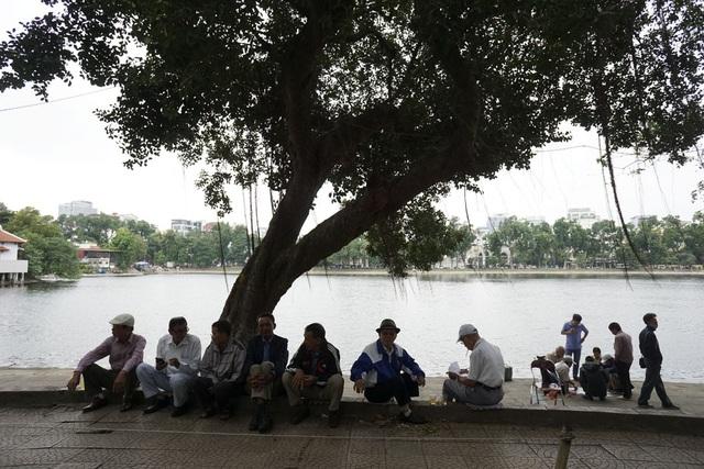 Một nhóm người cao tuổi với áo rét đang nghỉ ngơi bên hồ Thiền Quang.