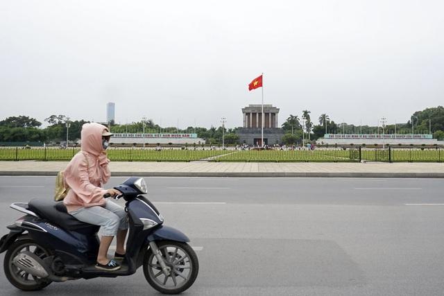 Trên quảng trường Ba Đình, gió thổi kèm không khí lạnh khiến người đi xe máy phải đưa tay kéo áo.
