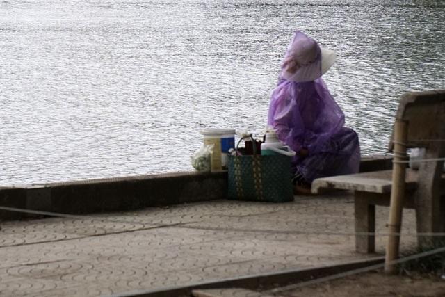 Người bán nước chè rong bên hồ phải co ro trong tấm áo mưa.