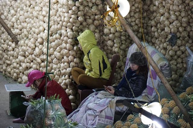 Những chủ buôn hoa quả ngồi co ro đợi bán hàng.