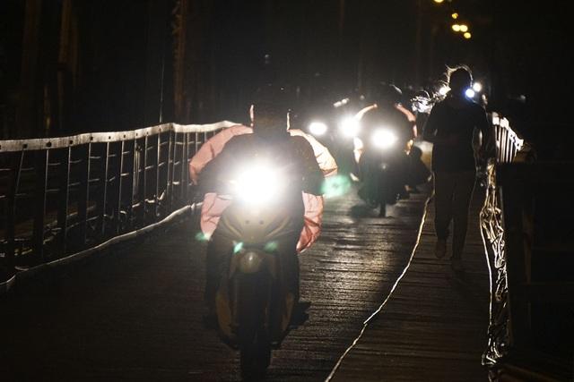 Cầu Long Biên về đêm. Lúc này không có mưa nhưng nhiều người đi xe máy mặc thêm áo mưa.
