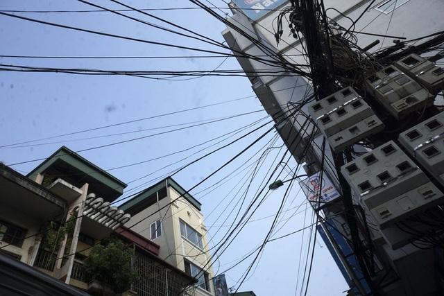 Từ một trụ điện, các loại cáp được chia như nan quạt, chạy thẳng vào các ngôi nhà trên phố. Ảnh chụp tại phố Nguyễn An Ninh (quận Hoàng Mai).