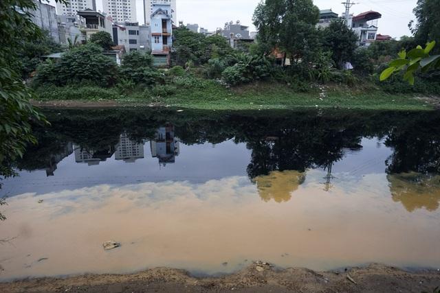 Mặt sông Nhuệ loang lổ những đám màu của các loại nước thải chưa qua xử lý tại khu vực xóm Cầu, xã Hữu Hòa, huyện Thanh Trì.
