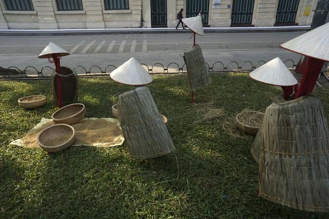 Hình ảnh người nông dân lam lũ qua nghệ thuật sắp đặt với áo tơi, nón lá.