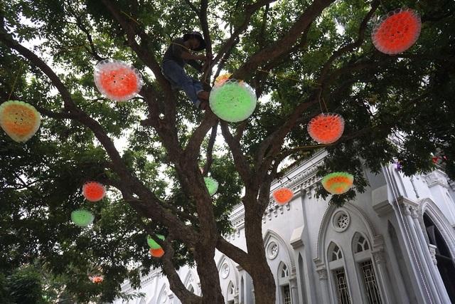 Các chùm đèn nhiều màu sắc được gấp rút lắp quanh nhà thờ.