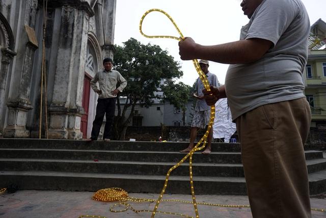 Các giáo dân làng Đông Lao đang chuẩn bị những dây đèn ống sẽ được treo lên xung quanh nhà thờ. Nhà thờ này là nơi hành lễ cho khoảng 80 hộ gia đình công giáo trong làng, chiếm tỷ lệ chưa đến 10%.