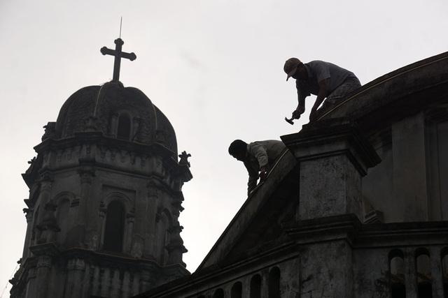 Bóng dáng các giáo dân đang hối hả trang trí bên tháp chuông nhà thờ.