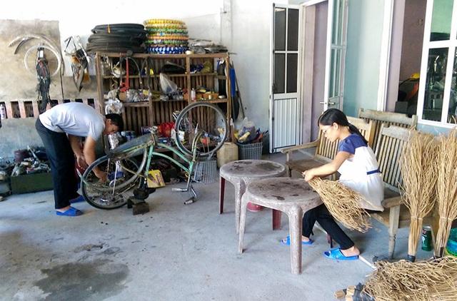 Thầy Sơn sửa xe đạp trong khi vợ thầy bó chổi kiếm thêm thu nhập.