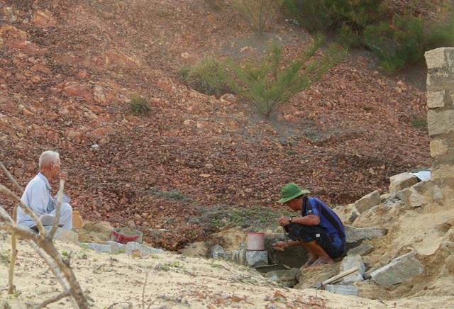 Người dân đang xây tường bao quanh chặn cát, đá bồi lấp vào mộ