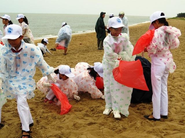 Hàng trăm học sinh Trường THCS Ngô Quyền và Tiểu học Bạch Đằng (TP Tuy Hòa, tỉnh Phú Yên) mặc áo mưa nhặt rác làm sạch bãi biển Tuy Hòa