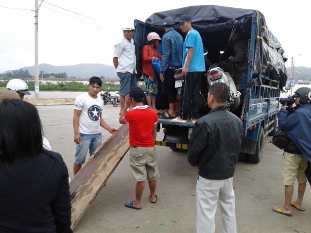 Người dân phải mất 20.000 đồng/người/xe máy/lượt để xe tải đưa qua đập Huỳnh Mai (huyện Tuy Phước) bị ngập trong lũ - ảnh chụp: chiều tối 4/11