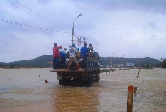 Xe máy và người được đưa lên xe tải băng qua tràn Huỳnh Mai trong nước lũ