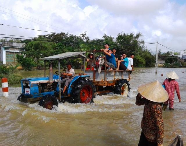Nhiều nơi giao thông vẫn bị chia cắt, người dân phải đi lại bằng thuyền hoặc xe máy cày để vượt lũ