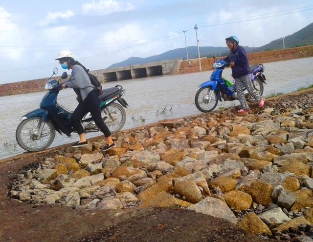 Người dân phải dắt bộ qua đoạn đường hư hỏng nặng do lũ