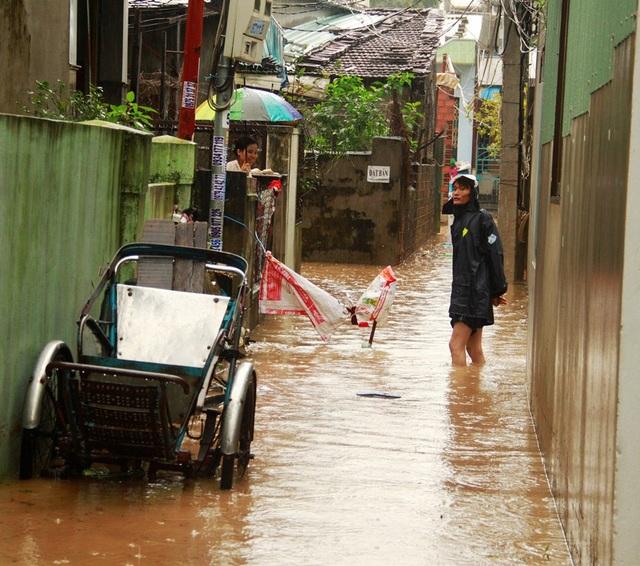 Dù trời mưa nhưng anh Thanh mặc áo mưa trong nước lạnh để cảnh báo người dân không đi vào khu vực có hố ga bị hư