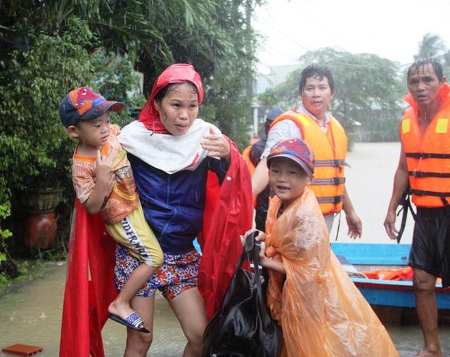 Chị Nhì tay bế con trai 5 tuổi vừa thoát khỏi nhà bị ngập nhưng vẫn lo đàn heo trong chuồng bị nước ngập