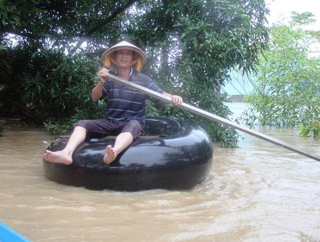 Một người dân dùng săm ô tô bơm hơi lên làm phao di chuyển trong nước lũ