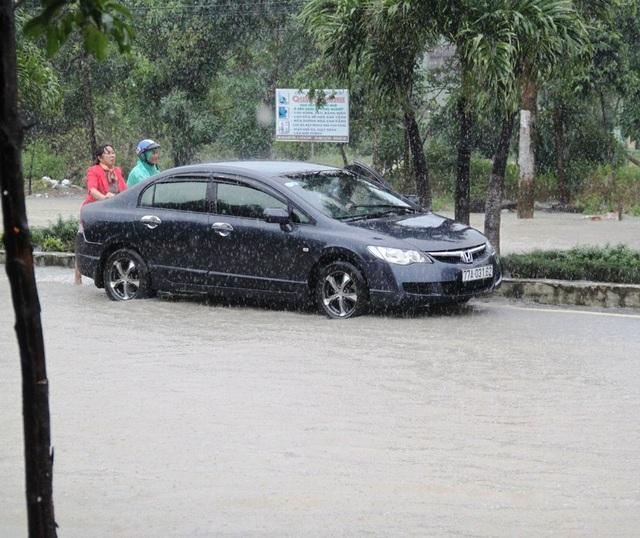 Quốc lộ 1 đoạn qua phường Trần Quang Diệu và Bùi Thị Xuân (TP Quy Nhơn) nước ngập sâu, một ô tô bị chết máy phải xuống xe đẩy qua dòng nước lũ cả 300 m