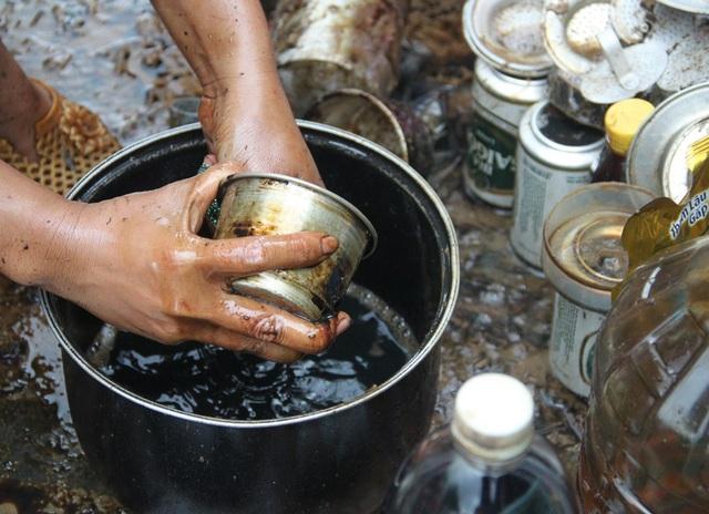 Bà Thu chùi rửa từng món đồ bị bám dầu nhớt