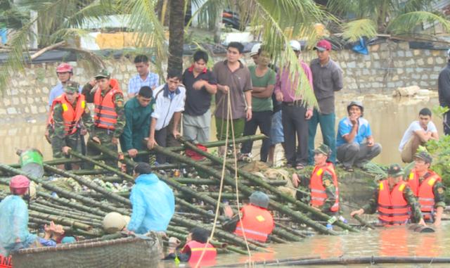 Các chiến sĩ bộ đội, công an ngâm mình trong lòng nước lũ đưa bè cá để khơi thông dòng chảy qua cầu Thiện Chánh