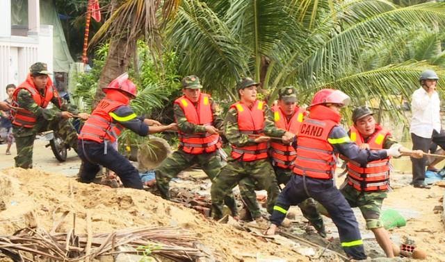 Các chiến sĩ nỗ lực kéo tàu cá bị lũ nhấn chìm
