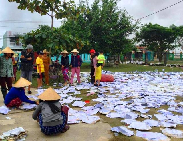 Phụ huynh học sinh ở huyện Phù Cát bơi sách vở bị ướt do lũ