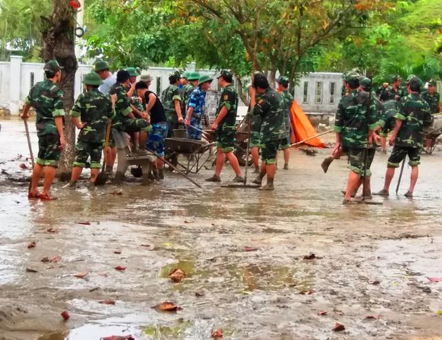 Lực lượng bộ đội huyện Tuy Phước giúp thầy cô giáo Trường Tiểu học số 1 Phước Thắng dọn bùn sau lũ