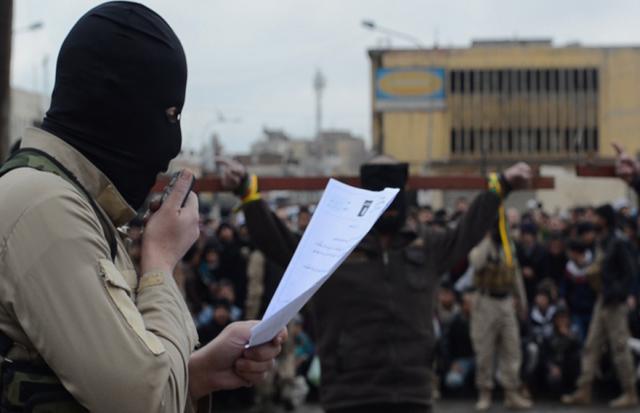 Một chiến binh IS đọc to cáo trạng tòa án Sharia ban hành trước khi hành quyết công khai nạn nhân (Ảnh: Iraqi News)