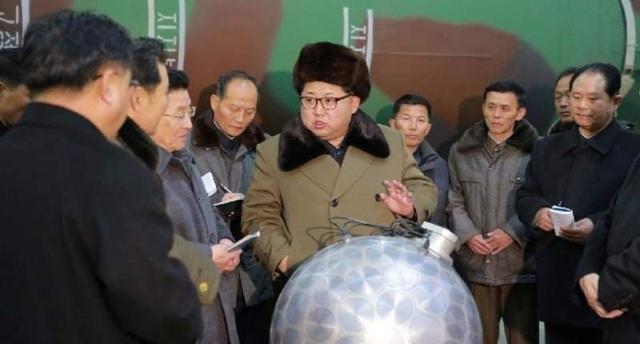 Nhà lãnh đạo Triều Tiên Kim Jong-un trao đổi cùng các chuyên gia bên cạnh một đầu đạn hạt nhân (Ảnh: BBC)