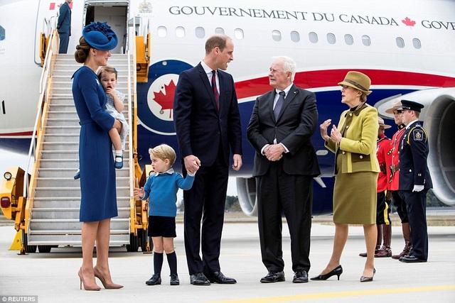 Công chúa Charlotte mặc váy màu xanh nhạt, được mẹ bế trên tay. Công chúa nhỏ tỏ ra hơi nhút nhát trong chuyến đi tới một đất nước xa lạ. (Ảnh: Reuters)