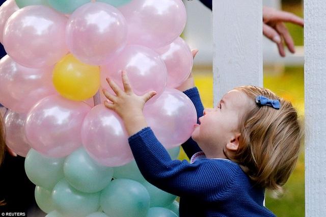 Công chúa Charlotte rất thích những quả bóng bay trang trí ở cổng chào và có vẻ muốn ôm chúng về nhà.
