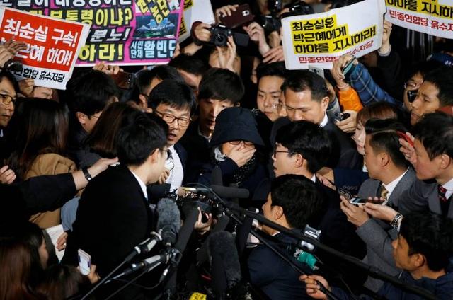 Bà Choi Soon-sil (đội mũ) trong vòng vây báo chí khi xuất hiện tại văn phòng công tố ở Seoul (Ảnh: Koreatimes)