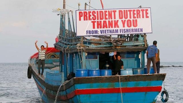 Ngư dân Việt Nam vui mừng sau khi được Philippines trả tự do. Tấm biển ghi dòng chữ cảm ơn Tổng thống Rodrigo Duterte được gắn trên một con tàu. (Ảnh: AFP)