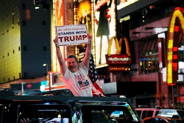 Một người đàn ông giơ cao tấm biển ủng hộ ông Trump khi ngồi trên xe chạy qua Quảng trường Thời đại ở New York. (Ảnh: Reuters)