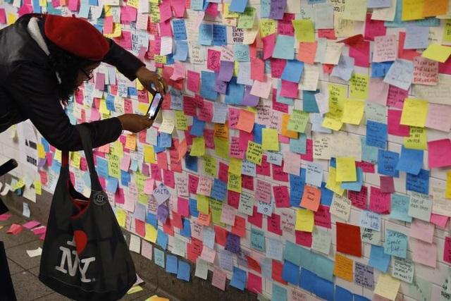 Một phụ nữ chụp lại lời nhắn của mình (Ảnh: Reuters)