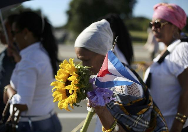 Nhiều người mang theo cờ, hoa và di ảnh của cố Chủ tịch Fidel Castro khi đi cùng dòng người tiến vào Đài tưởng niệm Jose Martin ở thủ đô Havana.