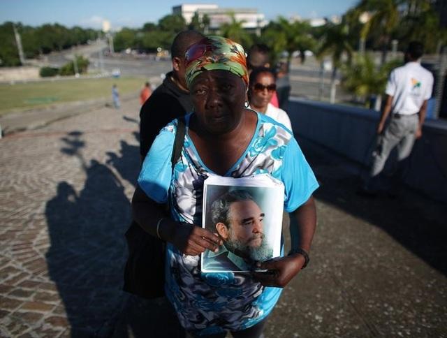 Một người phụ nữ cầm trên tay di ảnh của lãnh tụ Fidel Castro khi xếp hàng vào viếng ông.